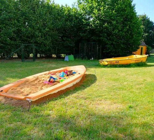 Bauernhof mit Sandkastenboot im Garten